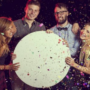 Group of friends having fun, celebrating New Year's Eve and holding a blank cardboard circle